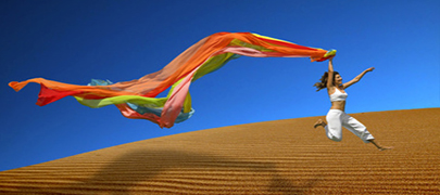 Beautiful woman jumoping over the sand dunes with a colored scarf